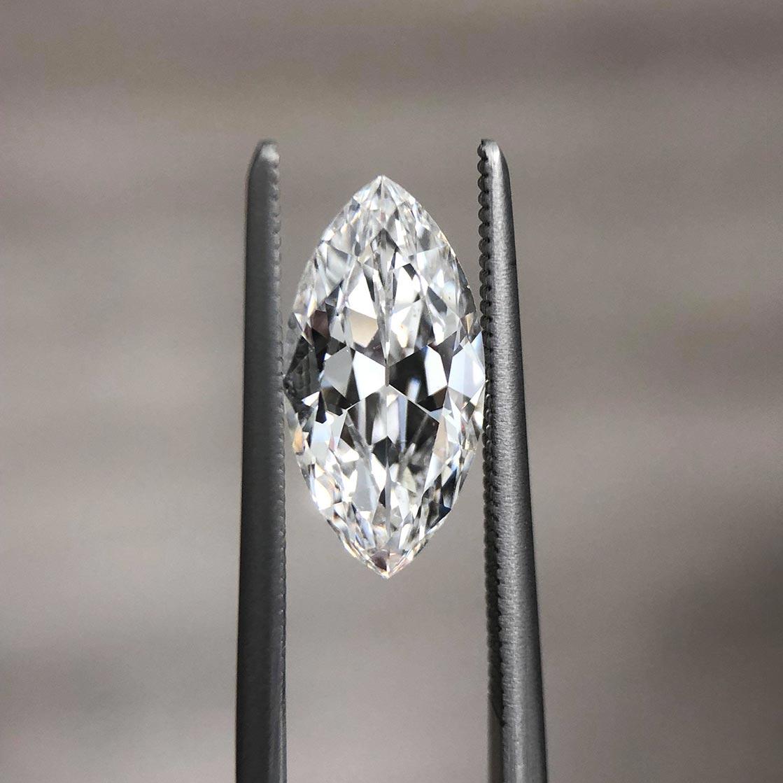 Loose white marquise diamond held in a pair of tweezers