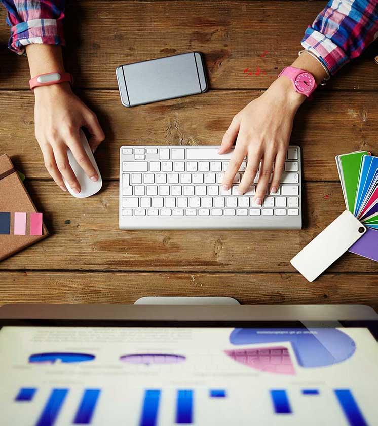 Woman typing on keyboard using SEO graphs.
